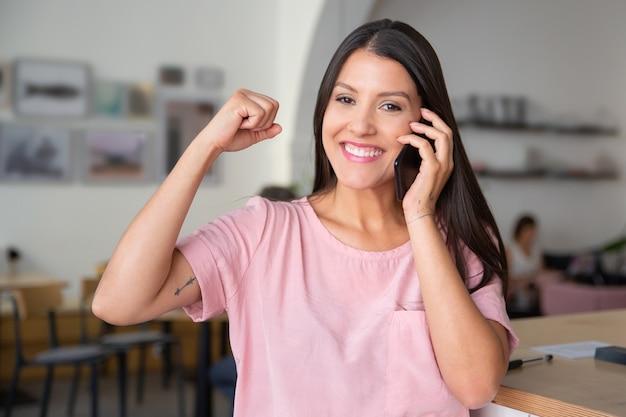 Mulher bonita, feliz e bem-sucedida falando no celular, cerrando o punho na mão, gesto vencedor, em pé no espaço de trabalho conjunto