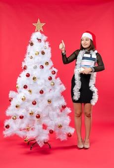 Mulher bonita feliz e surpresa em um vestido preto com chapéu de papai noel e perto de uma árvore de natal decorada