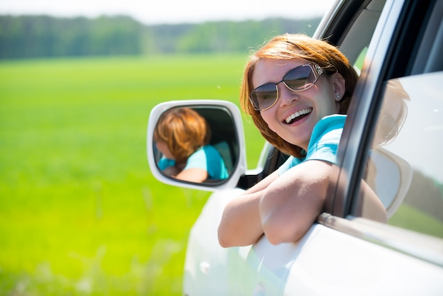 Mulher bonita feliz em carro novo branco na natureza
