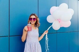 Mulher bonita feliz em óculos de sol, beber uma bebida fresca, segurando um monte de balões de ar