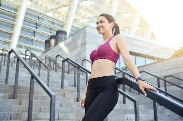 Mulher bonita feliz em um top esportivo e legging em pé ao ar livre