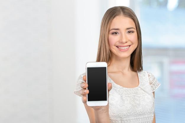 Mulher bonita feliz mostrando uma tela do telefone inteligente em branco