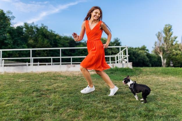 Mulher bonita feliz no parque correndo com o cachorro boston terrier, sorrindo, humor positivo, estilo de verão moderno, usando um vestido laranja, brincando com um animal de estimação, se divertindo, colorido, férias ativas de fim de semana, tênis