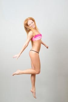 Mulher bonita feliz pulando em traje de banho. retrato de uma jovem em um fundo cinza.