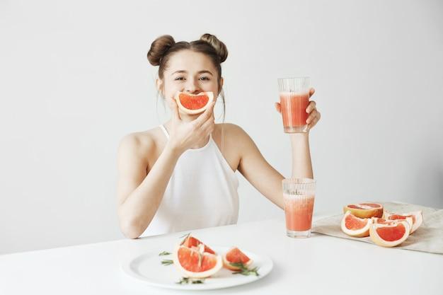 Mulher bonita feliz que senta-se na tabela que guarda o batido fresco da toranja da desintoxicação saudável sobre a parede branca.
