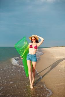 Mulher bonita feliz se divertindo na praia, vestindo roupas de praia elegantes, biquíni e shorts jeans, pernas longas, corpo magro e apto, segurando o colchão de ar e caminhando perto do oceano.