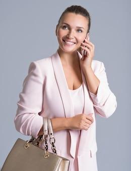 Mulher bonita feliz segura bolsa e celular sobre branco.