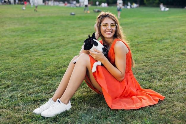Mulher bonita feliz sentada na grama no parque de verão, segurando o cachorro boston terrier, sorrindo, humor positivo, usando um vestido laranja, estilo moderno, pernas finas, tênis, brincando com o animal de estimação