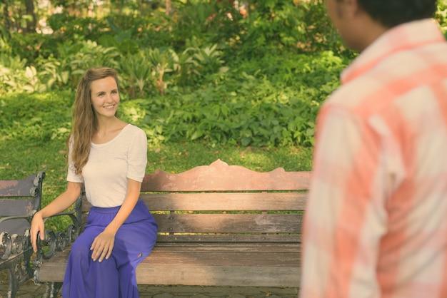 Mulher bonita feliz sorrindo e sentada no banco de madeira enquanto olha para o homem indiano apaixonado no tranquilo parque verde