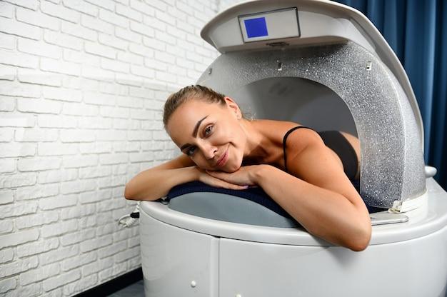 Mulher bonita feliz sorrindo para a câmera deitada na cápsula do spa, desfrutando de um tratamento de beleza profissional no salão do spa