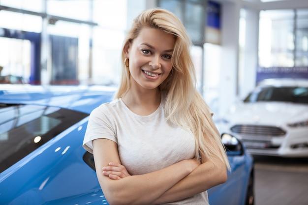 Mulher bonita feliz sorrindo para a câmera em pé na frente de seu novo automóvel na concessionária.