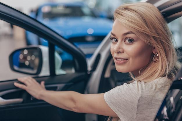 Mulher bonita feliz sorrindo para a câmera, sentado em um automóvel novo no salão do automóvel
