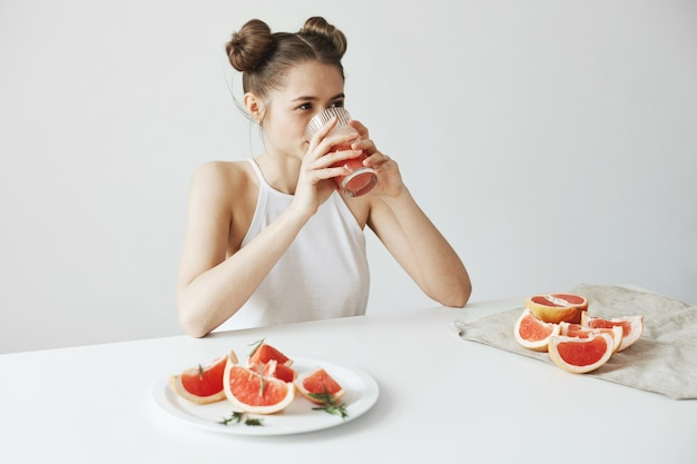 Mulher bonita feliz sorrindo sentado à mesa, bebendo suco de toranja fresca de desintoxicação saudável sobre parede branca.
