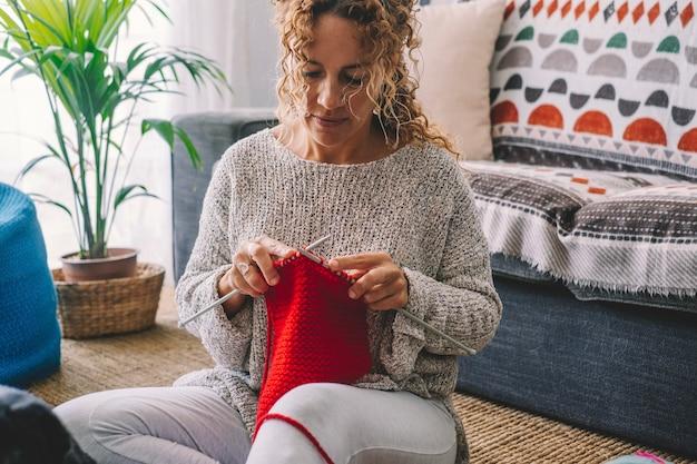 Mulher bonita feliz sorrir e admirar sua lã colorida vermelha de sagacidade de trabalho de malha. mulheres gostam de atividade de lazer de tricô interno em casa na temporada de inverno