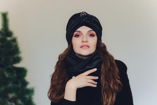 Mulher bonita feliz surpresa, olhando de soslaio em emoção. menina do natal que desgasta o chapéu morno feito malha e as luvas, isoladas no fundo cinzento.
