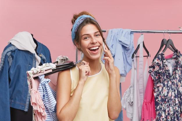 Mulher bonita feliz tendo dia de compras, escolhendo muitas roupas para comprar, conversando com alguém por telefone inteligente, sorrindo amplamente, regozijando-se com grandes descontos em loja e boa compra