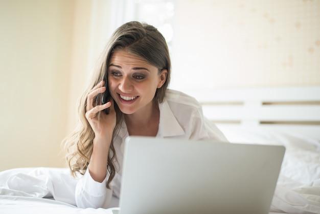 Mulher bonita feliz trabalhando em um laptop na cama em casa