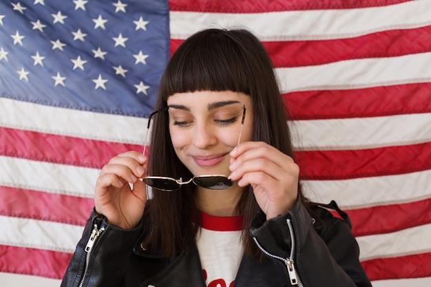 Mulher bonita feminina ou adolescente usa novos óculos de sol na frente da bandeira americana, moderno e moderno, patriota dos eua