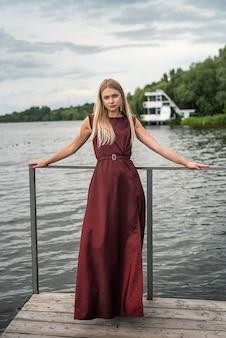 Mulher bonita fica com um vestido longo vermelho escuro na natureza. conceito de viagens.