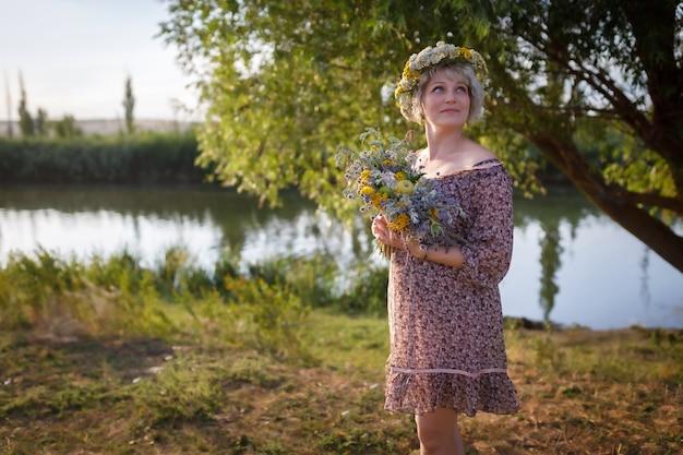 Mulher bonita fica na margem do rio com um buquê de flores silvestres