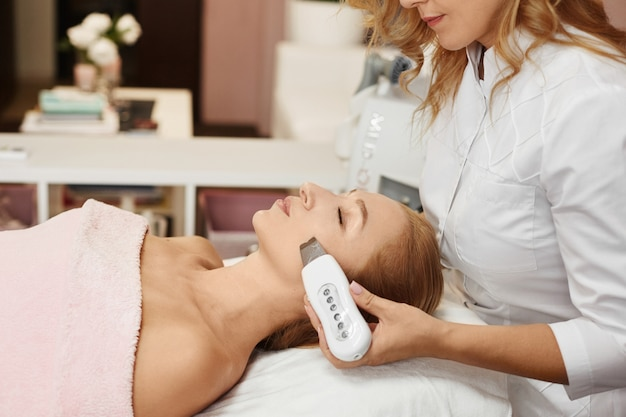 Mulher bonita, ficando o rosto descascando o procedimento em uma clínica de beleza, procedimento não cirúrgico facelifting. tratamento facial rejuvenescedor.