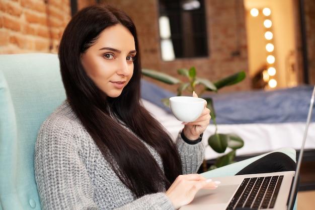 Mulher bonita ficar em casa e trabalhando em um laptop, bebendo café