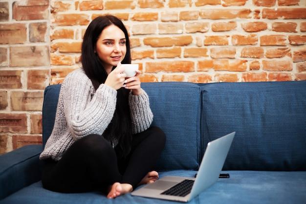 Mulher bonita, ficar em casa e trabalhando no laptop on-line