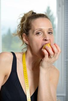 Mulher bonita fitness com fita métrica e apple