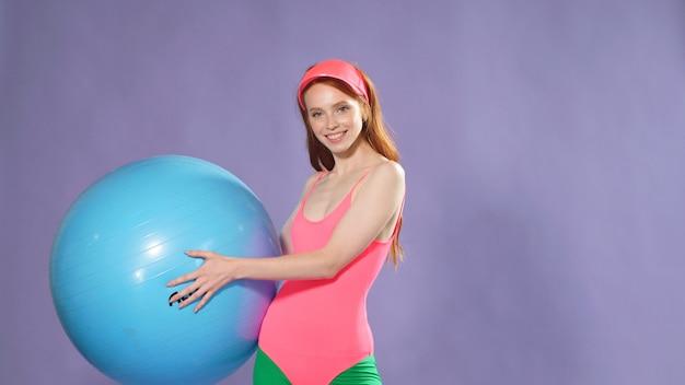 Mulher bonita fitness exercícios com uma bola no ginásio