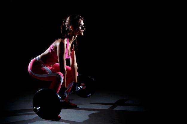 Mulher bonita fitness fazendo agachamentos com uma barra