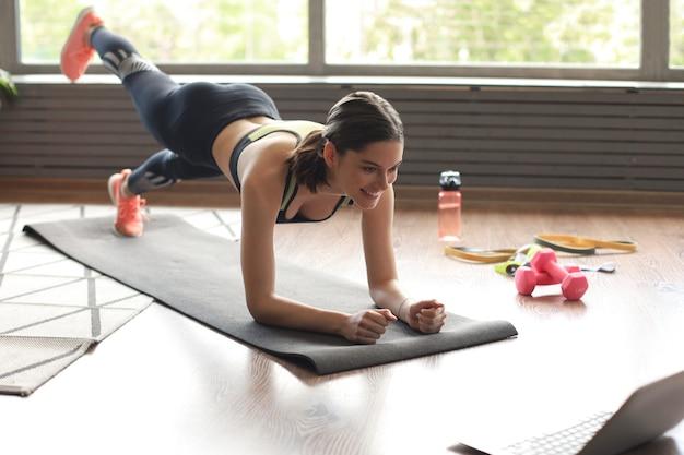 Mulher bonita fitness fazendo um exercício de prancha assistindo tutoriais on-line no laptop, treinando na sala de estar. estilo de vida saudável. a garota pratica esportes em casa.
