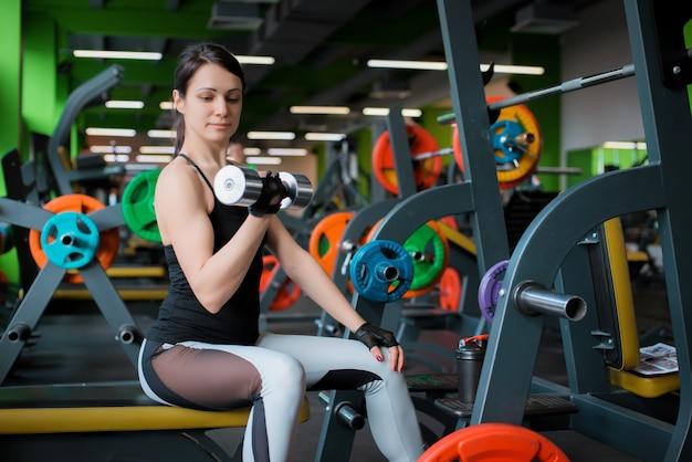 Mulher bonita fitness levantando a barra. mulher desportiva levantando pesos. menina apta exercitando os músculos do edifício. fisiculturismo fitness