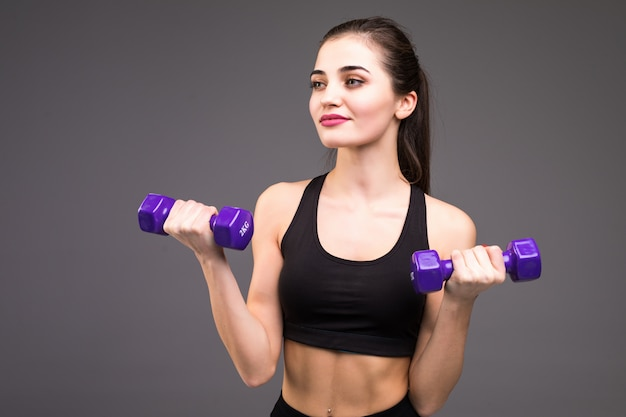Mulher bonita fitness tonificar exercícios com halteres na parede cinza