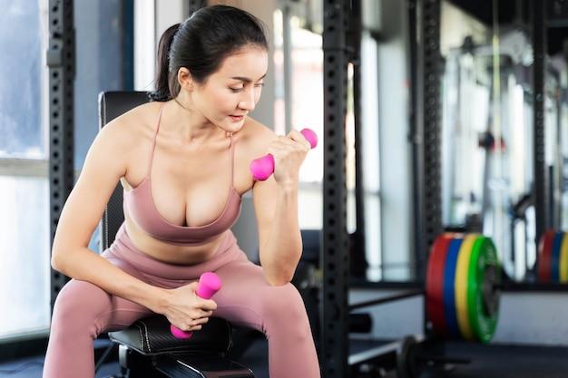 Mulher bonita fitness trabalhando push up com halteres em uma sala de ginástica, corpo magro de garota sexy asiática - conceito de modelo de fitness. Foto Premium