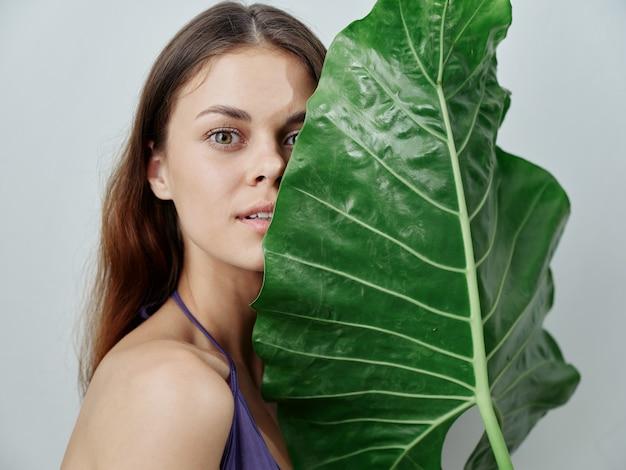 Mulher bonita folha de palmeira verde perto do rosto ombros nus pele clara trópicos