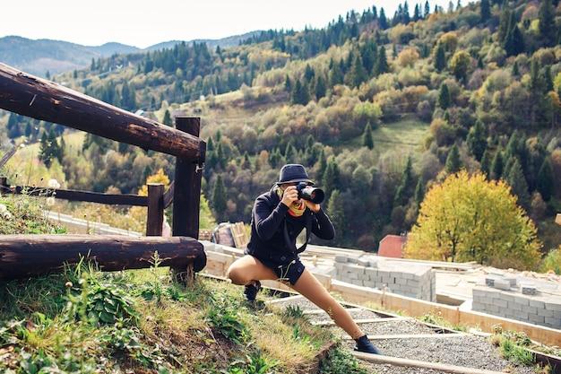 Mulher bonita fotografa a natureza na montanha no outono.