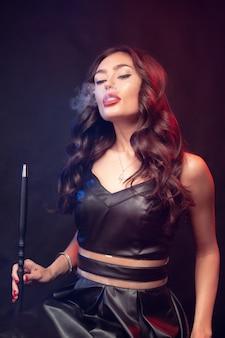 Mulher bonita fuma cachimbo de água ou shisha. vape nuvem branca.