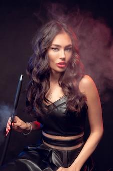 Mulher bonita fuma cachimbo de água ou shisha.