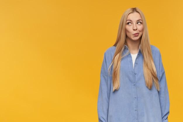 Mulher bonita, garota curiosa com longos cabelos loiros. vestindo camisa azul. conceito de emoção. franze os lábios, tenha pensamentos complicados. observando à esquerda no espaço da cópia, isolado sobre fundo laranja