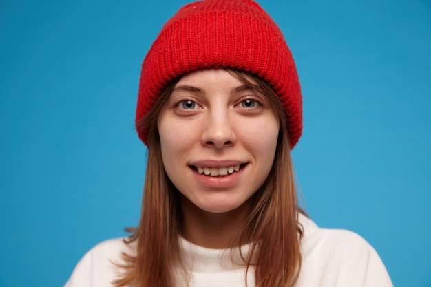 Mulher bonita, garota feliz com cabelo castanho. vestindo um suéter branco e um chapéu vermelho. pessoas e conceito emocional.