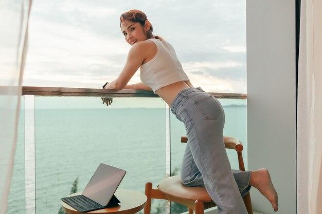 Mulher bonita gosta de olhar a vista do mar da varanda do hotel