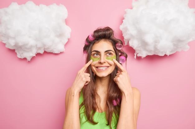 Mulher bonita gosta de procedimentos de cuidados com a pele - pontos em manchas de colágeno verde sob os olhos - faz penteado antes de uma ocasião especial, concentrado acima, isolado sobre a parede rosa