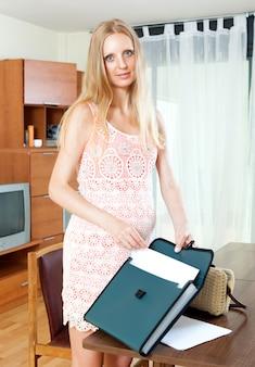 Mulher bonita grávida com documento em papel na sala de estar