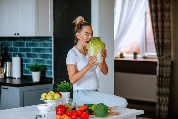 Mulher bonita grávida em camisa branca e jeans com pão sentado em uma mesa da cozinha e mordendo o repolho fresco. felicidade.