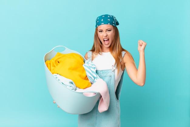 Mulher bonita gritando agressivamente com uma expressão de raiva segurando um cesto de roupa suja