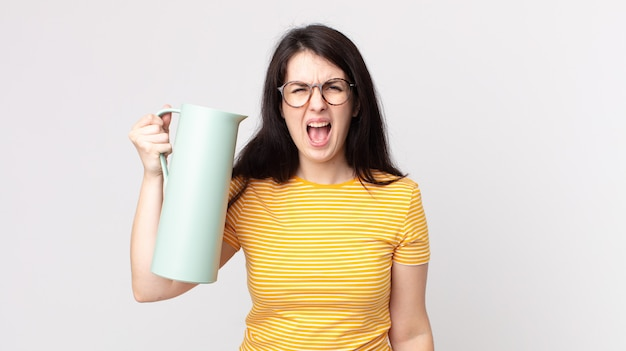 Mulher bonita gritando agressivamente, parecendo muito zangada e segurando uma garrafa térmica de café