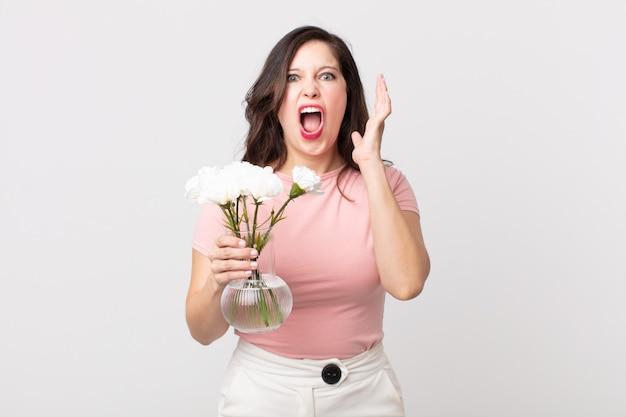 Mulher bonita gritando com as mãos para o alto e segurando um vaso de flores decorativas