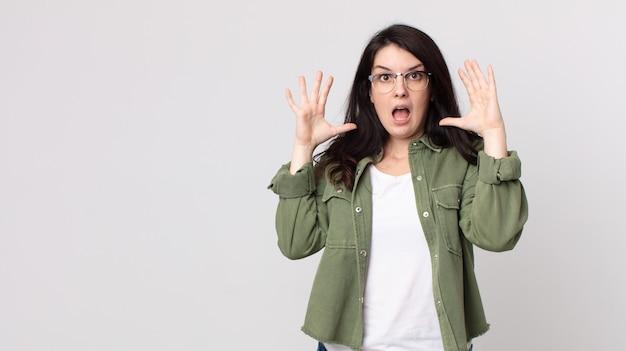 Mulher bonita gritando com as mãos para o alto, sentindo-se furiosa, frustrada, estressada e chateada
