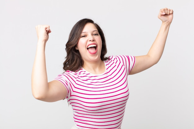 Mulher bonita gritando triunfantemente, parecendo vencedora animada, feliz e surpresa, comemorando