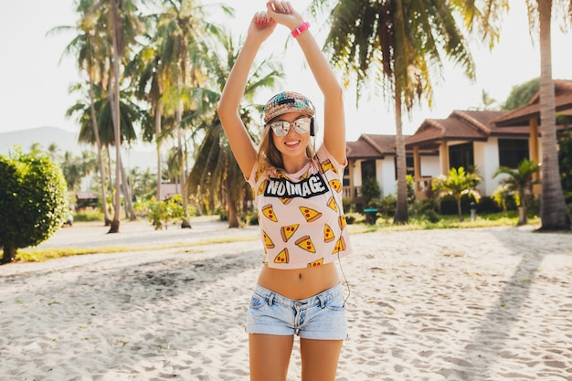 Mulher bonita hippie andando na praia, dançando ouvindo música em fones de ouvido, com roupa colorida elegante em férias tropicais de verão ensolarado usando óculos de sol com acessórios, sorrindo se divertindo